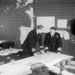 THE ROYAL NAVY DURING THE SECOND WORLD WAR (A 25742) Commander Cross, Staff Officer Convoys, (left) discussing a special convoy movement map with Captain Lake, RN, Duty Officer in the Operations Room at Derby House, Liverpool.
